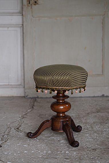 房飾りが付いたスツール-antique round stool 球根型の脚に重きを置いて、如何にもな生地で張り替えるとかっちり、クラシカル過ぎるきらいが。ウォールナット材の美しい木目に合わせ、シックなモスグリーン生地に少し遊んだフリンジ飾りを縁取りに。所作を綺麗に見せる背もたれ無しのスツールはお化粧台用の椅子やエントランスの腰掛けとなされたら。座面直径はw350mm、一部新たにクッションを入れ替えての張替えです。回転し、高さ調整可能です。