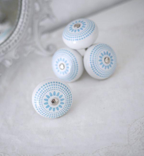 Vit rund porslins knopp med turkos /blått retro mönster likt en blomma. Med silver färgad metall stomme. I grepp vänlig modell.