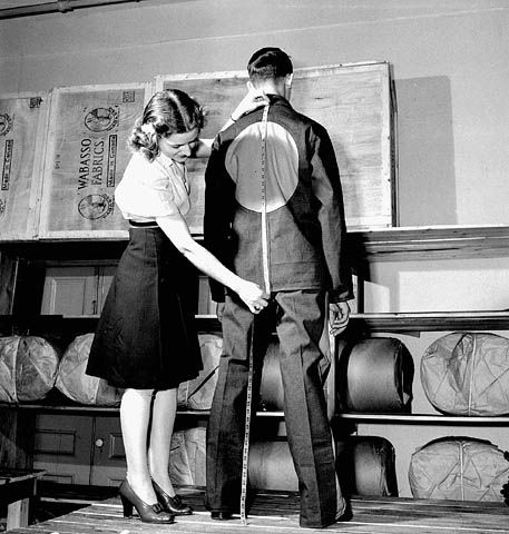 Woman worker measures back of man modelling internment uniform at the Standard Overalls Company. 1943, Montréal.  copyright expired (Credit: Ronny Jaques / National Film Board of Canada. Photothèque / Library and Archives Canada / PA-116152)