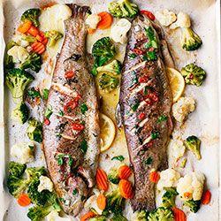 Pieczony pstrąg z masłem chili i warzywami. Pieczony pstrąg z warzywami i aromatycznym masłem z dodatkiem posiekanej papryczki chili, natki i czosnku.