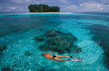 Snorkeling in clear waters infront of the small and uninhabited island of Dondola, Togian Islands, Sulawesi, Indonesia.