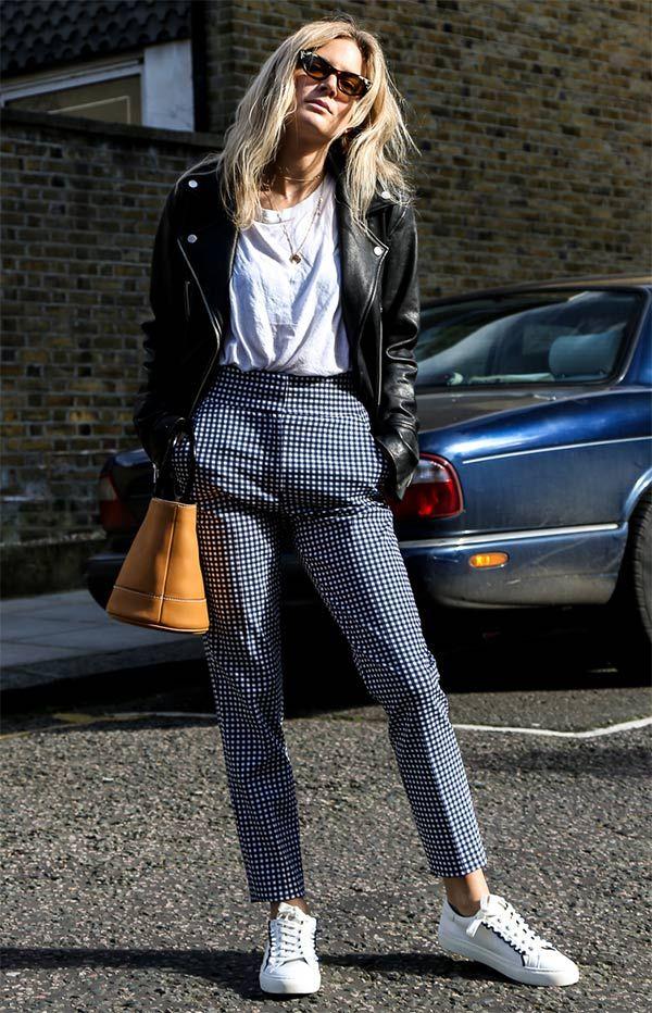 Lucy Williams usa calça xadrez, t-shirt branca, jaqueta de couro e tênis branco.