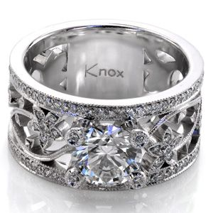Freesia - A magnificent piece that is all sparkle, Design 2297 features a 1.25 carat round center stone. The unique wide band features a floral pattern and lots of micro pave side stones; you'll be mesmerized by them. Each of the prongs even has a single small diamond set into it surrounded by milgrain!