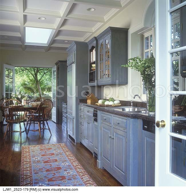 KITCHEN Looking Through French Doors Toward Table And Chairs Patio Beyond Coffered Ceiling Skylight Wood Floors Granite Countertop Rug Colonial