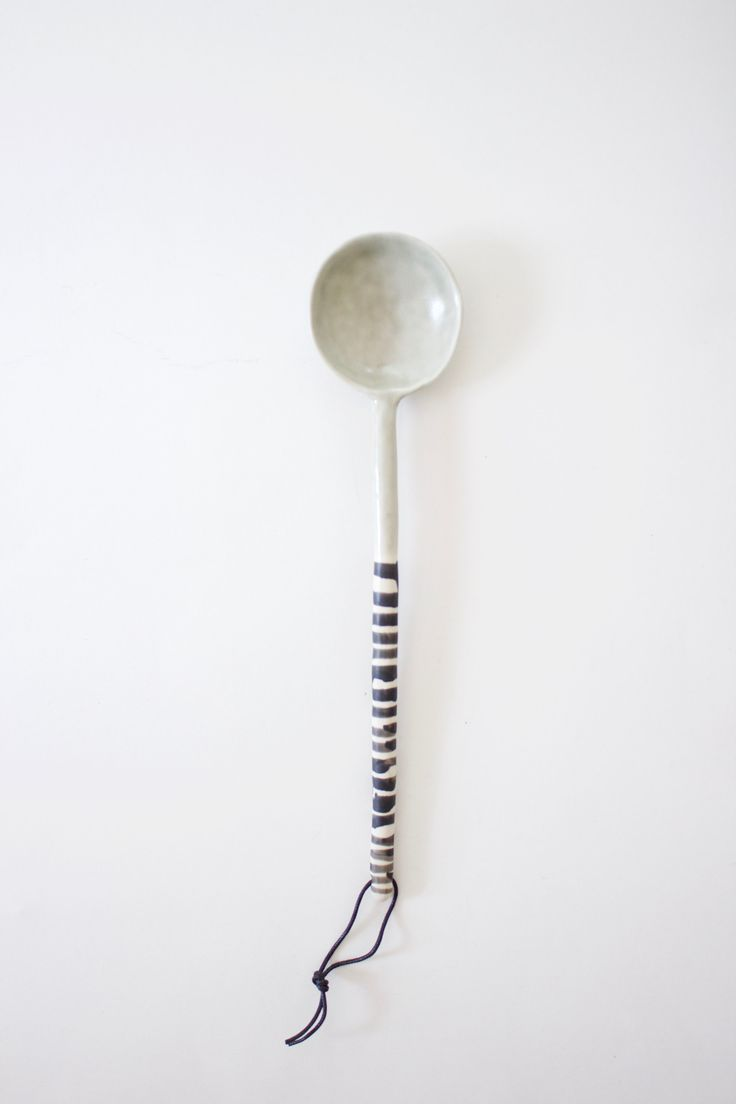 Long handled serving spoon made of ceramic clay in a mute sage hue, with a hand painted black and white striped handle. Handmade in small batches by Elizabeth Benotti in her studio in New Hampshire. -