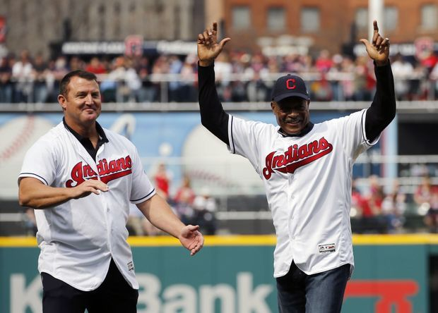 Former Cleveland Cavaliers guard Austin Carr raises his arms after throwing out the ceremonial first pitch with Jim Thome, left, and Jim Brown.  April 11, 2017  (Gus Chan / The Plain Dealer)