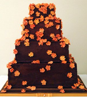 Brides.com: . This square hazelnut torte cake with chocolate mousse and hazelnut praline filling is frosted with chocolate truffle and decorated with a smattering of vibrant orange sugar blossoms. Cake by Alice's Tea Cup