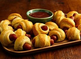 Mini Dogs: 2 cans Pillsbury® refrigerated crescent dinner rolls  48 cocktail-sized smoked link sausages or hot dogs (from 16-oz package)  Directions: Heat oven to 375°F. Unroll both cans of the dough; separate into 16 triangles. Cut each triangle lengthwise into 3 narrow triangles. Place sausage on shortest side of each triangle. Roll up each, starting at shortest side of triangle and rolling to opposite point; place point side down on 2 ungreased cookie sheets. Bake 12 to 15 minutes