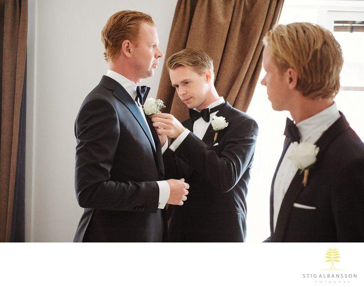 Företagsfoto - Porträttfoto - Bröllopsfotograf - Marskalker hjälper brudgum med blomma på rockslaget: Beata & NiklasLocation: Fjällbacka. Keywords: Bröllopsfoto (9).
