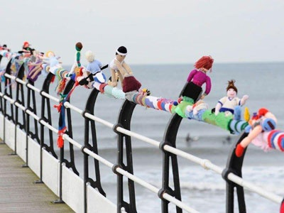 Yarnbombing  Olympic athletes at Saltburn Pier by the Yarn Junki    The pier at Saltburn, a seaside town in North Yorkshire, was transformed by a 50-metre scarf of knitted Olympic athletes in March 2012 - the knitted figures were busy doing everything from swimming to track events to weight-lifting. Hundreds of tourists flocked to the pier to see the spectacle