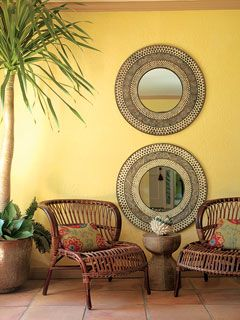 Warm colors and Southwestern-style furnishings make this sitting area a great place to relax. Two round mirrors lend visual interest and symmetry to the space, and the cool yellow paint color complements the tile floor.