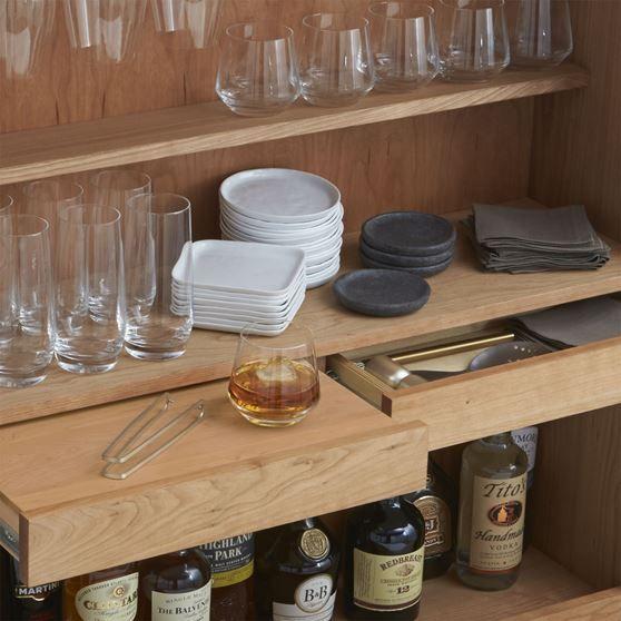 """18. yüzyıl ortalarında kurulan ve modern tasarım sürecinde önemli rol oynayan """"Shakers tarikatı""""nın yaşam ve dekorasyon tarzından etkilenen İngiltereli tasarımcı Russel Pinch, Victuel gri bar dolabını yarattı. Kaliteli şaraplar, değişik içkiler, şık bardaklar ve bar aksesuarları için ayrılmış bölmelerin olduğu dolap, unutulmaz partiler için gerekli donanıma sahip. Ürün, 24 şarap şişesi alabilen şarap rafları, bir düzine içki şişesi alabilen kapak içi bölmeleri var."""