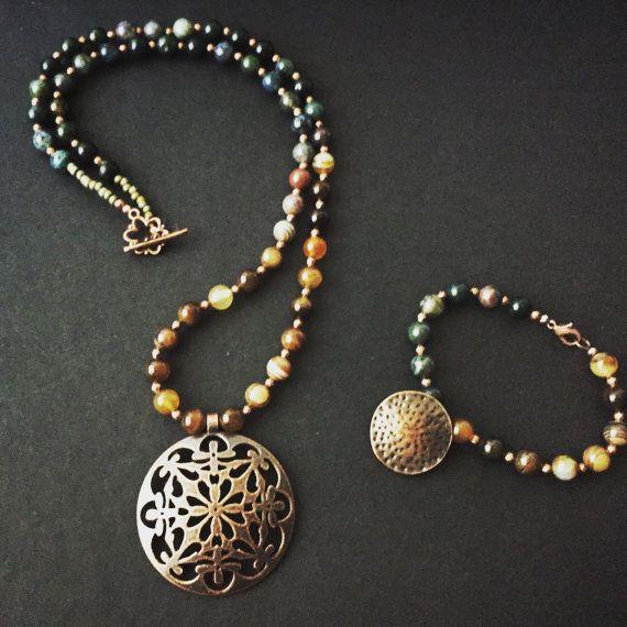 Collana realizzata con pietre di agata verde e marrone intercalate da piccole perline in rame. Il ciondolo è un cerchio traforato color rame anticato.  Bracciale disponibile