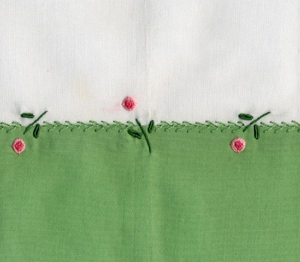 Constrasting green poplin hem is sewn to the lower edge of a skirt.  Featherstitch is worked over the seam and accented with pinwheel flowers. Made by Trudy Horne