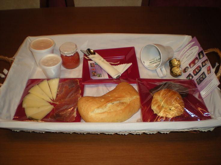 Desayuno Sorpresa compuesto por zumo de naranja, café Nespresso, tomate rallado, jamón, queso, pan de chapata, curasán y curasán de chocolate, bombones y una taza de porcelana, todo en una cesta de mimbre!