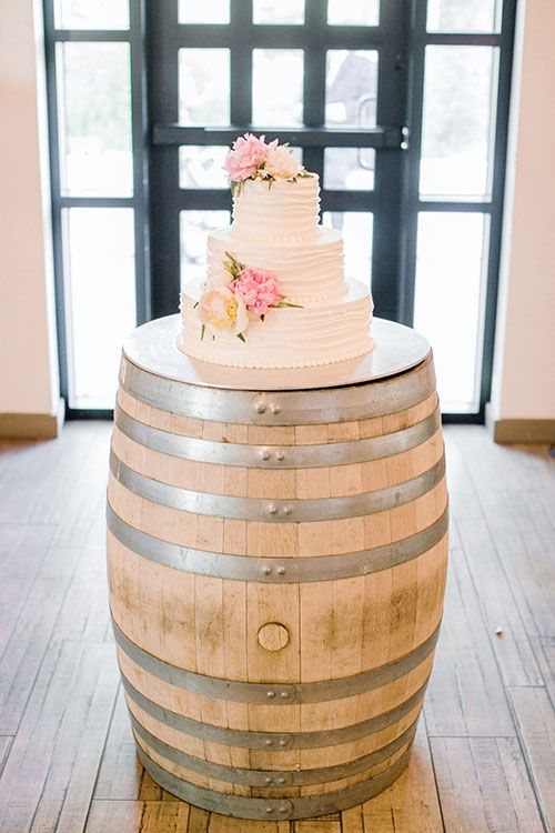 A three-tiered white wedding cake with pink flowers | @clanegessel | Brides.com