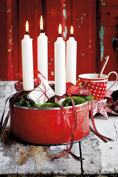 I en gammel kagedåse har vi lagt en våd oasis og derefter pudemos ovenpå. Fire almindelige, hvide stearinlys med et sødt bånd omkring er stukket ned imellem mosset. De små æsker er tændstikæsker, som vi har pakket ind i lidt julepapir – hver æske gemmer på en overraskelse, én for hver adventsøndag. Bånd fra Garden Shop. FOTO: STINNE HEILMANN
