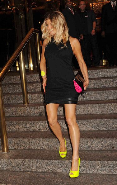 Fergie wears a short black dress and neon green heels as she leaves the Trump Hotel in NYC.