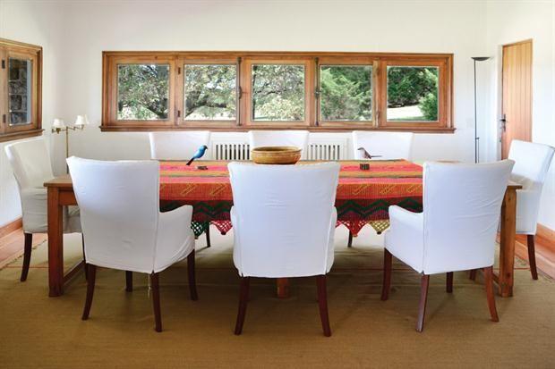 Tres casas con estilo campo  La gran mesa para ocho comensales está vestida con una manta artesanal. Las ventanas apaisadas con carpinterías en madera miran a la espectacular arboleda que rodea la casa..