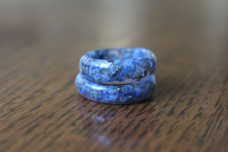 LAPIS LAZULI RING This once polished Lapis Lazuli was crushed, and the crystal chunks were placed throughout an entire eco resin ring.  SYMBOLIC MEANING Lapis Lazuli is a very spiritual stone and is known to open the third eye and balance the throat chakras. This leads to enlightenment and self confidence as it helps in finding your true voice. It teaches the power of spoken word. It has also been used to contact spiritual guides.