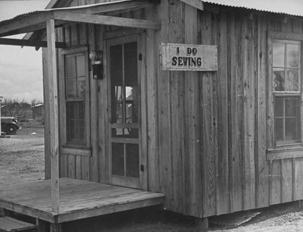 """Freer, Texas Wooden shack in oil boomtown, with sign that says """" I Do Sewing."""" Location: Freer, TX, US Date taken: 1937 Photographer: Carl M..."""