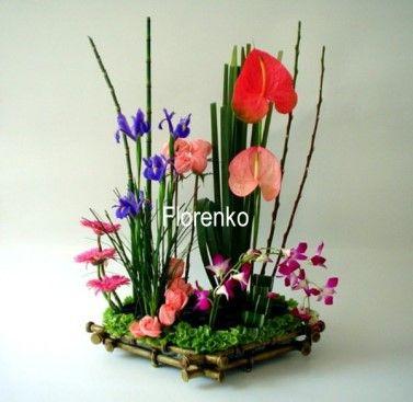 Artistica presentación de flores Exóticas en finísima base de acabado en bronce, realizado con; orquídeas, anturios, iris azules, bambus miniatura, gerberas , rosas y follajes seleccionados.