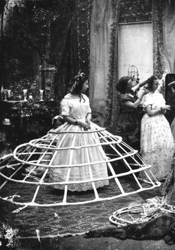 1860  The vast hoop skirts of the mid-19th century were supported by crinolines – steel, cage-like structures worn with a corset and petticoats. They were cumbersome and dangerous (it was tricky to sit down and to get in and out of carriages plus they could get trapped in machinery and catch fire) but at least they were lightweight and allowed the wearer's legs to move freely. The crinoline reached its maximum dimensions in 1860 and then started to shrink to less ludicrous proportions.: