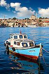 Fishing boat in the Golden Horn on the Galata banks looking towards the Suleymaniye Mosque (Süleymaniye Camii, 1550-1558)  on the Third Hill, Istanbul Turkey.