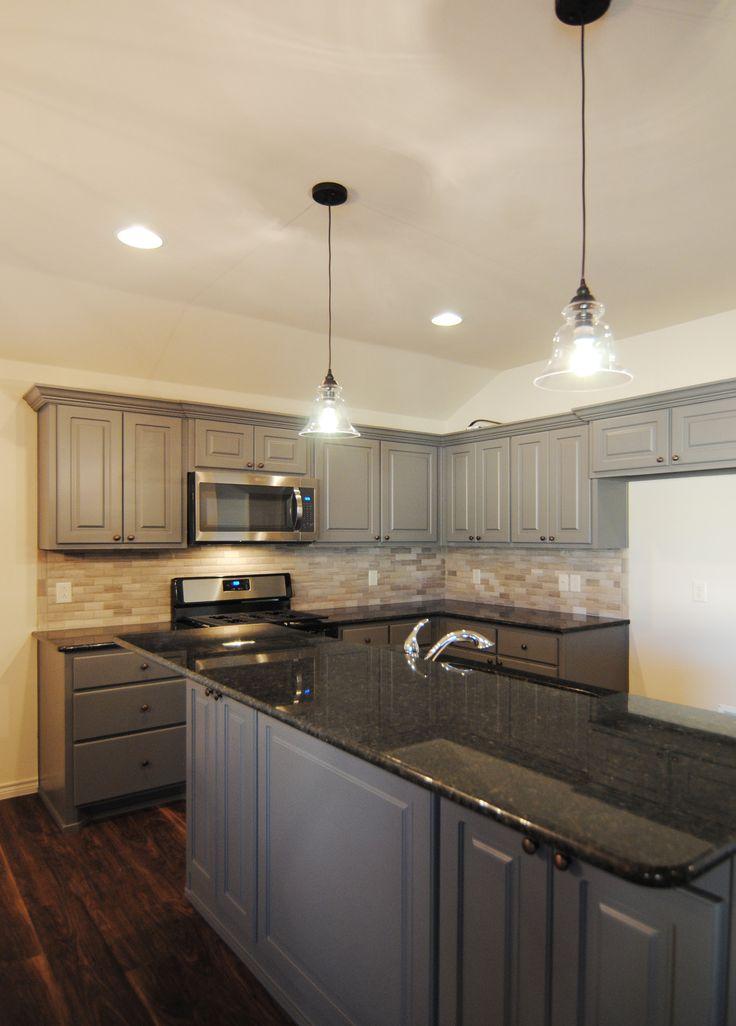 Kitchen by Ventura Homes in Cedar Park. granite / gray cabinets / stainless steel / gas range / over the range microwave / pendant lights / full back splash / vinyl plank flooring