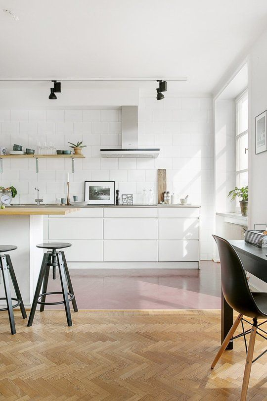 All-white modern Scandinavian kitchen with red concrete floors and open shelving.