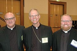 """Archbishop Etienne finds pioneer spirit, deep faith in Alaska""  Msgr. William F. Stumpf, archdiocesan administrator, left, Archbishop Paul D. Etienne of Anchorage, Alaska, and Father Joseph Newton, left, archdiocesan vicar judicial, pose for a photo before the start of the spring meeting of the U.S. Conference of Catholic Bishops in Indianapolis on June 14. (Photo by John Shaughnessy)"