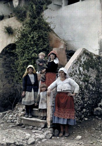 Three women pose with children on stone steps, Corfu