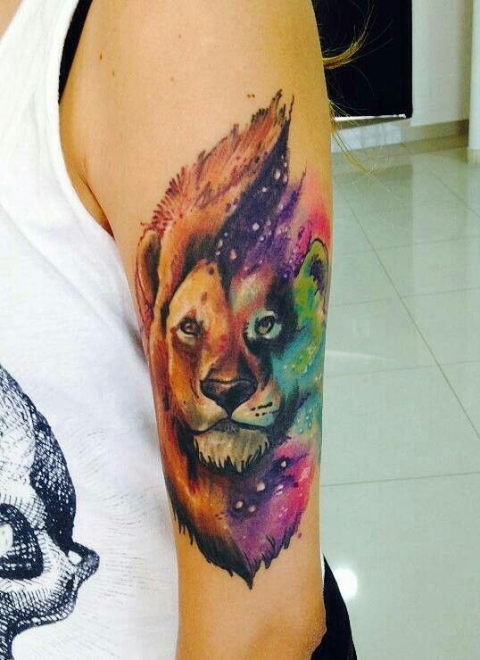 This colorful tattoo features a variety of colors with an ombre effect while still retaining the realistic facial features of a lion.
