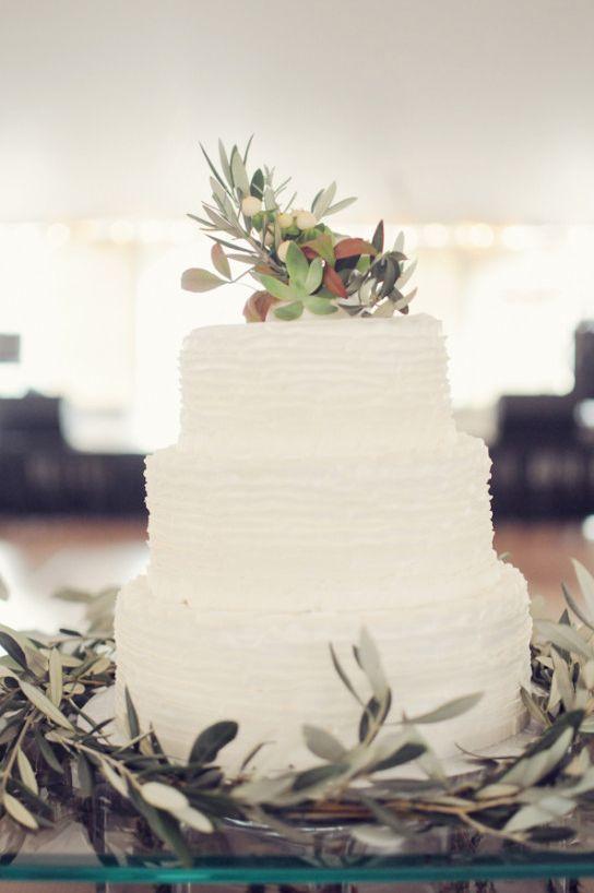 Tiered and textured white wedding cake with olive branches. #weddingcake #cakeideas #weddingchicks Captured By: Alea Moore Photography ---> http://www.weddingchicks.com/2014/04/29/family-farmhouse-wedding-retreat/