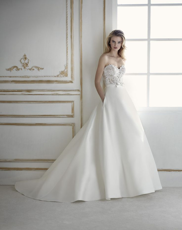 POMAL – LA SPOSA 2018 The most classic designs can also be very sensual, like this sleeveless ballgown-style wedding dress in mikado. A design with a fitted waist that combines two looks thanks to the waistband that marks the line between the skirt and the bodice. A sweetheart bodice in tulle with lace and guipure...  Citește mai mult »