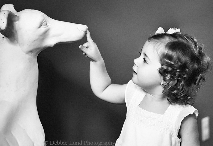 little girl with ceramic dog   black and white photography   natural light indoors