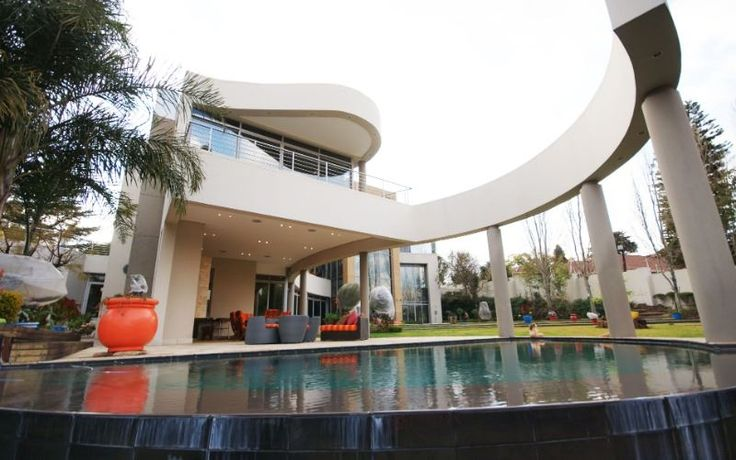 Spectacular residence with superb views of Sandton skyline  This triple-storey modern home offers a unique lifestyle. Secluded in an acre of landscaped garden in prestigious Bryanston East. The delightful open-plan receptions flow on to an entertainer's patio with heated rim-flow pool and manicured garden. The entertainment facilities include a bar with fireplace, billiard room and wine cellar.
