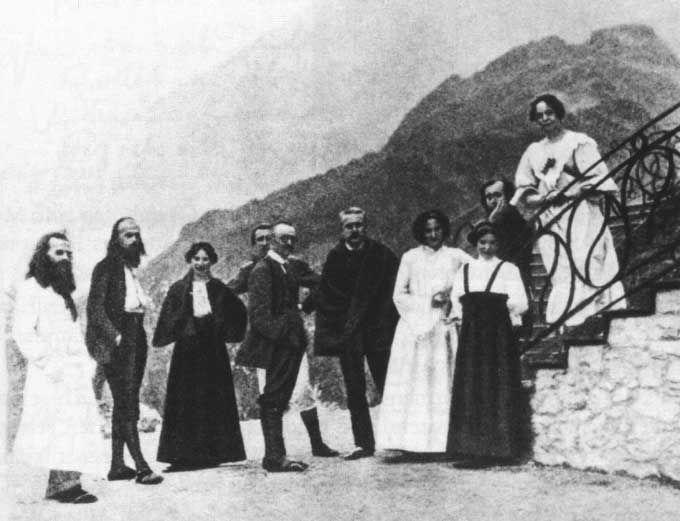 Hermann Hesse (centre de profil) au Monte Verità, en Avril 1907. Henri Oedenkoven et Ida Hofmann (2e et 3e en partant depuis la gauche). On reconnaît les ornements taoïstes (Yin-Yang) sur la balustrade du bâtiment principal. En haut à droite, la colline du Baladrüm.