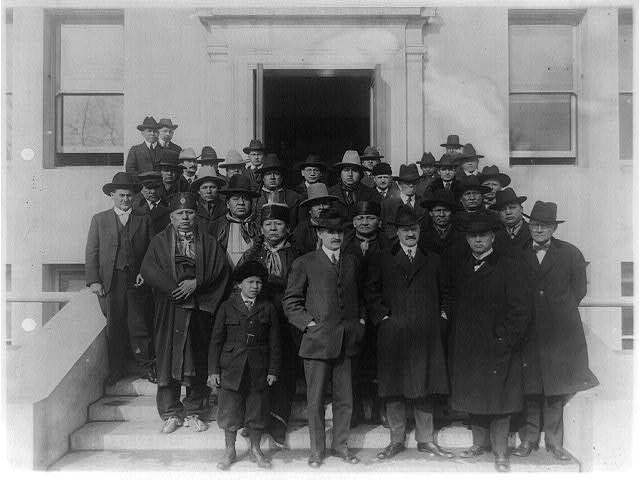 The Osage Council, with other Osage Indians, who came to Washington in connection with gas and mineral rights on the Osage Nation in Oklahoma. Commissioner of Indian Affairs Cato Sells, Assistant Commissioner E.B. Meritt and Superintendent of the Osage Nation J. George Wright are in foreground