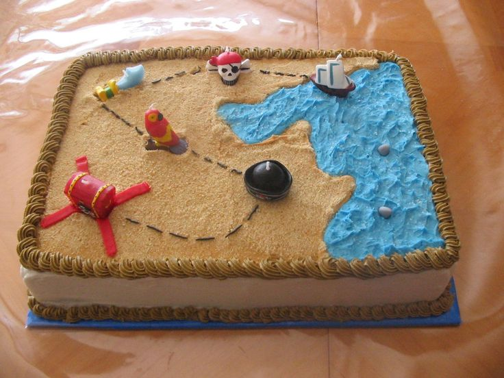 Pirate treasure map - This is a chocolate and yellow marble cake with BC. The water has cake sparkles and the sand is crushed vanilla cookies. The sharks are fondant and the rest are pirate themed candles.