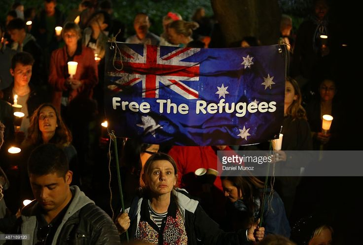 People hold candles and signs up in support of refugees on September 7, 2015 in Sydney, Australia. Thousands of people around Australia gathered to remember Aylan Kurdi, the young Syrian refugee who died last week and to protest the Australian Government's current refugee policy.