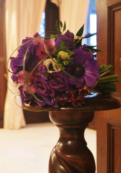 Luxurious deep purple hand-tied bridal bouquet. Lovely velvety-centred anemomes, lisianthus, statice, alstroemeria and bear grass looped over the top. Perfect for a country-house wedding. Florissimo, Shropshire