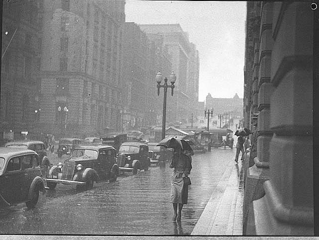 Rain, Martin Place, Sydney, 1937 / by Sam Hood Format: Film photonegative Notes: This image is taken from the corner of the post office looking up Martin Place east towards Macquarie Street. Martin Place was closed to traffic in 1971 and is now a pedestrian mall.