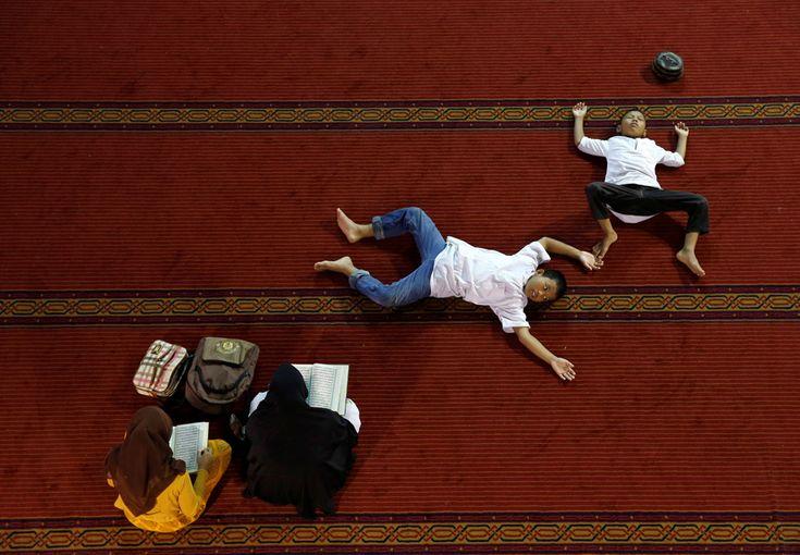 Mulher lê o Alcorão enquanto os rapazes descansam dentro da mesquita de Istiqlal durante o mês sagrado do Ramadão em Jakarta. Indonésia, 9 de junho de 2016. REUTERS/Beawiharta