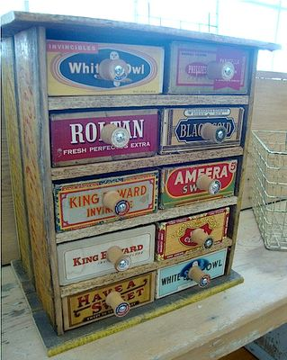 vintage cigar box cabinet with spool knobs!  I have several old cigar boxes that came from my grandparents.  You can't find them anymore.  This would be a cool idea to put the to use!