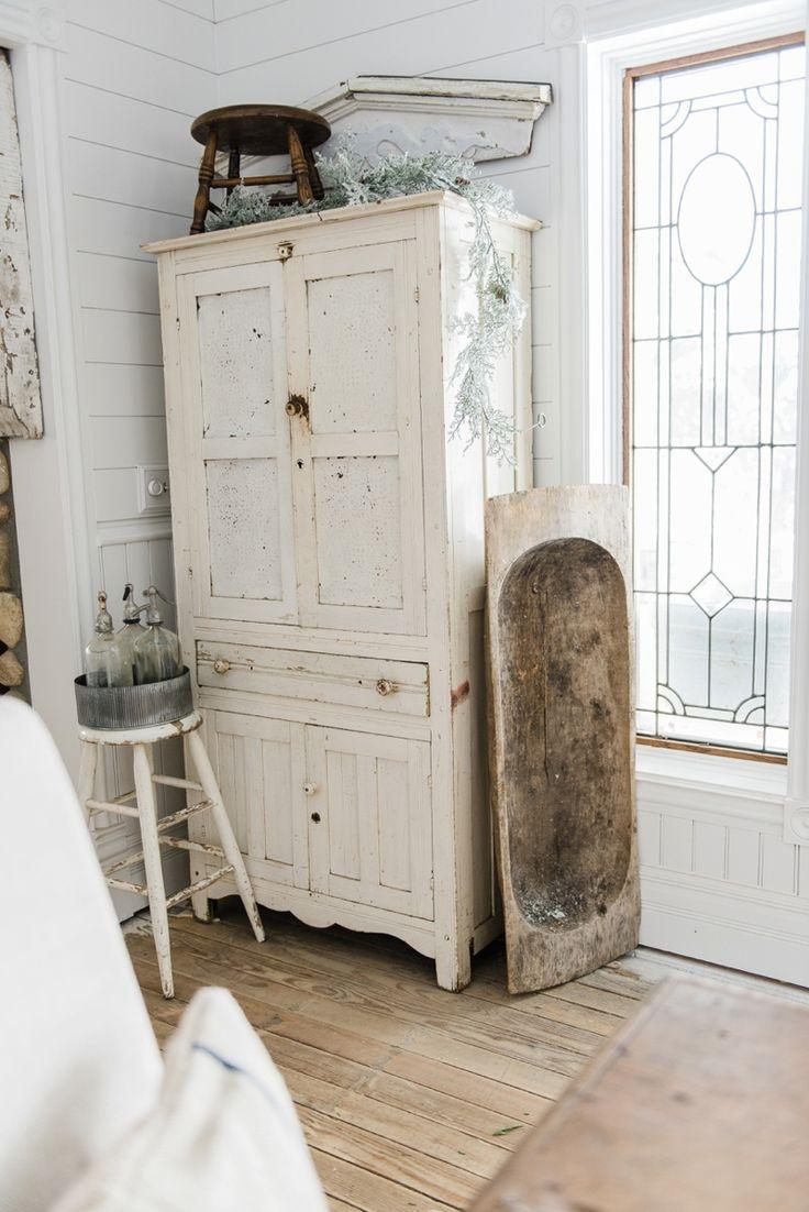 White chippy farmhouse cupboard - Farmhouse winter decor in a farmhouse dining room on LizMarieBlog.Com