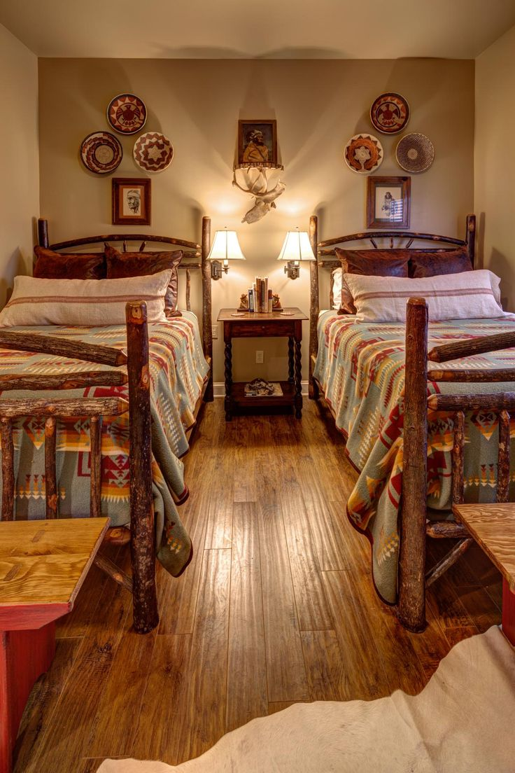 Rustic log beds create a lodge feel in this bedroom, while printed bed linens add Southwestern flair. Decorative plates coordinate with the bedding, tying the space together.