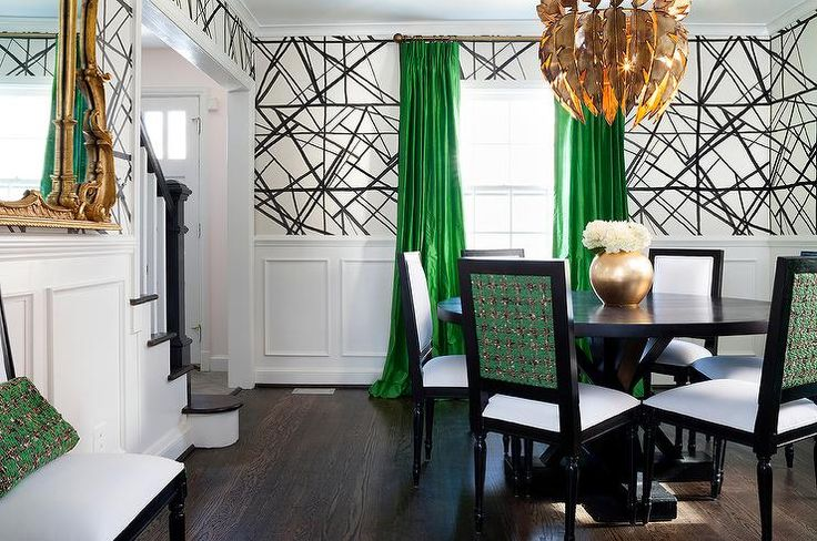 Green and black dining room features upper walls clad in black and white geometric wallpaper, Kelly Wearstler Channels Wallpaper, and lower walls clad in wainscoting.