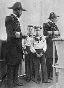 Deux hommes âgés en uniforme d'officier naval et portant un bicorne entourent deux enfants en uniforme de matelot.