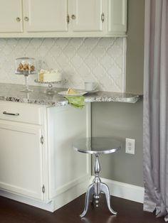 Bianco Antico Granite Countertop with White Cabinets, Beveled Arabesque Tile and Dark  Hardwood Flooring